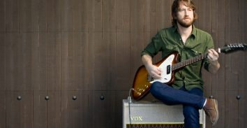artist, Chris Shiflett, sitting on VOX amplifier and playing electric guitar