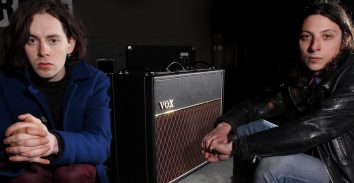 two musicians sitting on either side of VOX amplifier