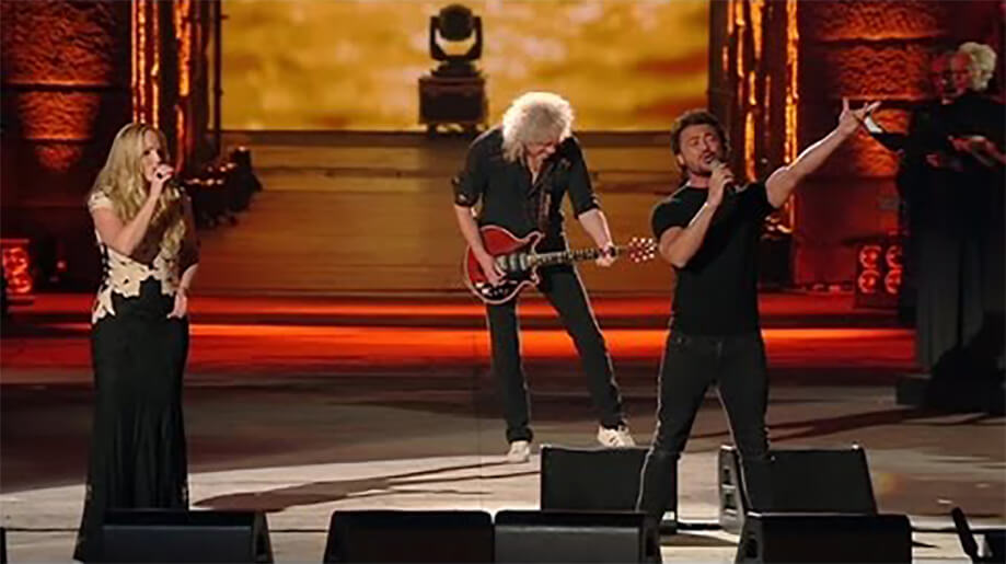 Brian May in concertbehind two singers