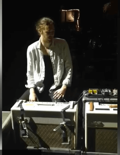 man sitting behind two VOX amplifiers