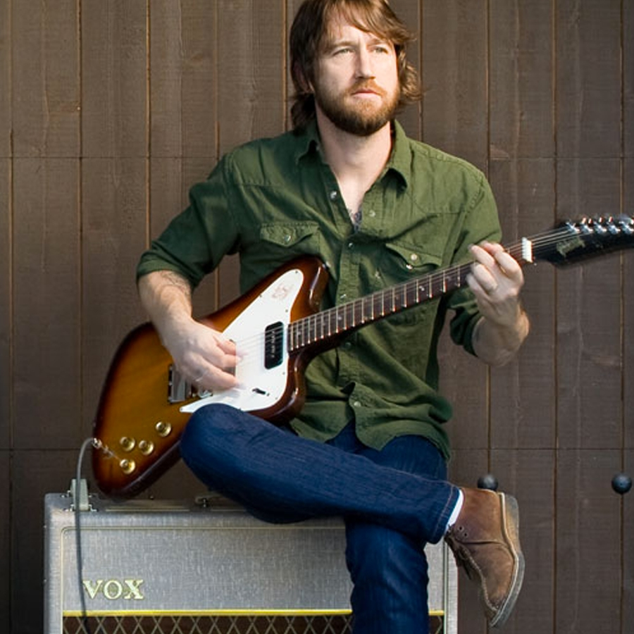 man playing electric guitar and sitting on VOX amplifier