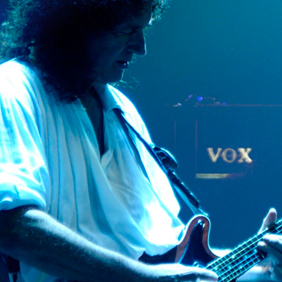 Musician, Brian May, playing electric guitar with a VOX amplifier behind him