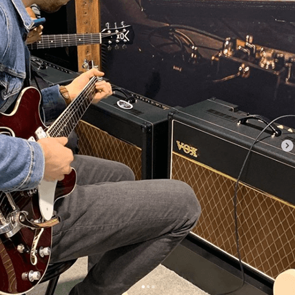 partial view of two men playing electric guitars in front of VOX amplifiers