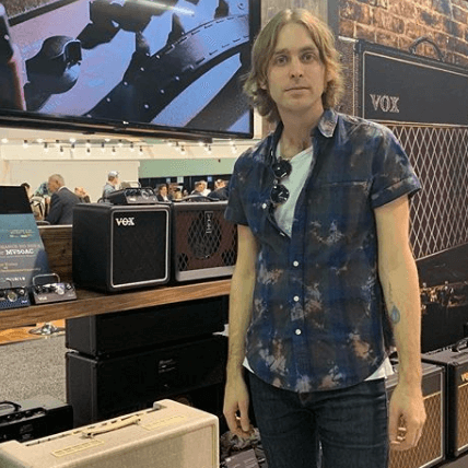 man standing next to various VOX products