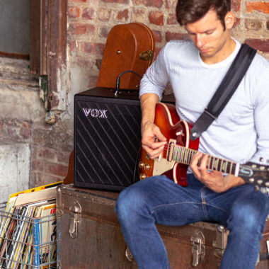Vox Cambridge50 guitar modeling amp sitting on a trunk to the left of a man playing an electric guitar