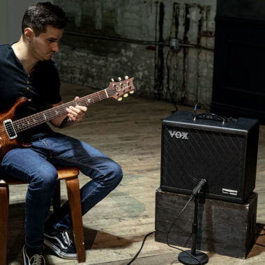 Vox Cambridge50 guitar modeling amp sitting to the right of a man playing an electric guitar