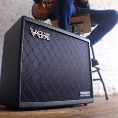 Vox Cambridge50 guitar modeling amp sitting on the floor in front of a man playing an electric guitar