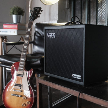Vox Cambridge50 guitar modeling amp on a table next to a sunburst electric guitar