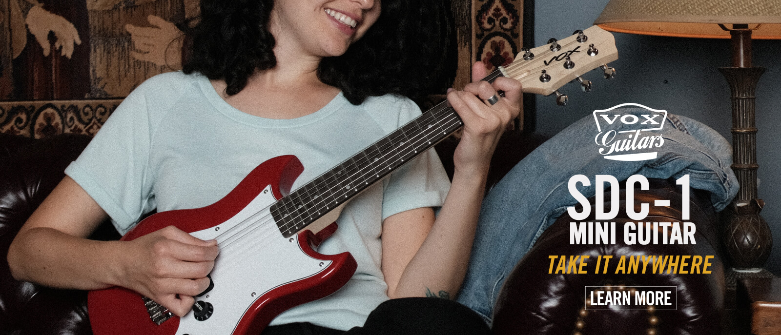 seated female musician playing red VOX SDC-1 Mini Guitar