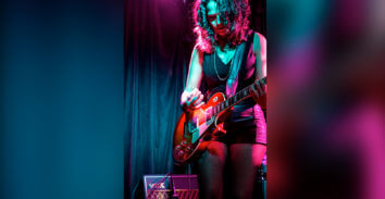 female musician playing electric guitar in front of VOX amplifier