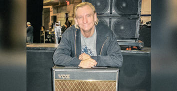 man leaning on VOX amplifier in front of stage