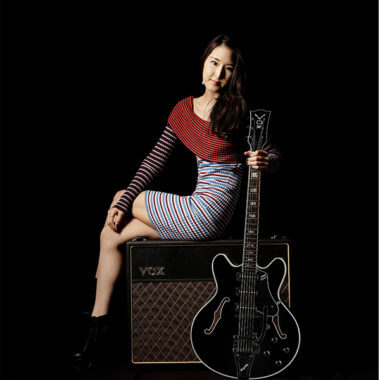 woman sitting on amp and holding electric guitar