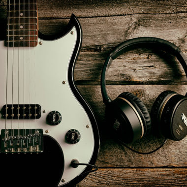VOX headphones beside electric guitar