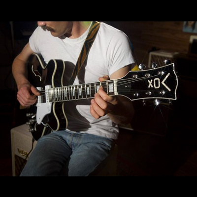 partial view of man playing black VOX electric guitar