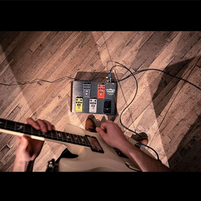 partial view of man playing electric guitar and footboard