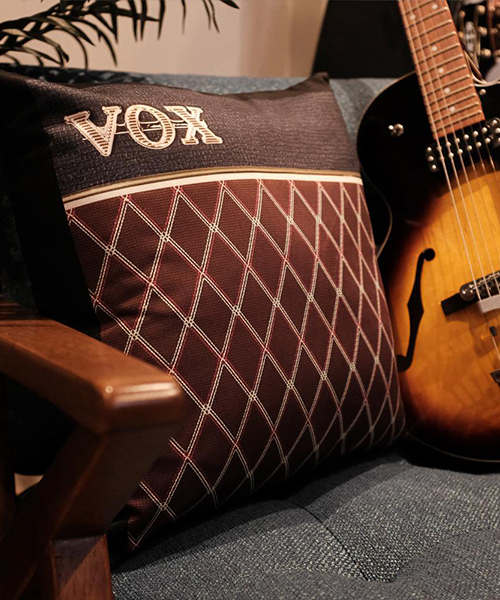 Vox throw pillow on a chair next to a guitar