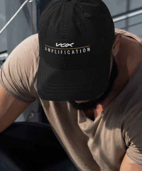 man wearing Vox Amplification hat looking down
