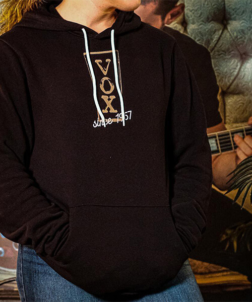 Person wearing Vox hoodie with hands in pockets