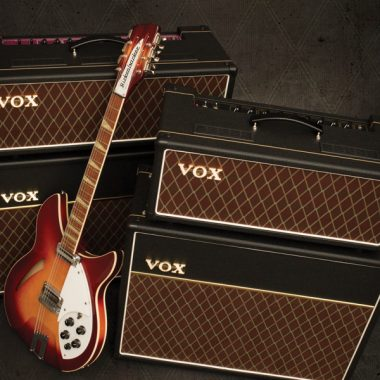 electric guitar leaning up against two VOX amplifiers