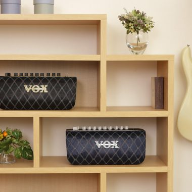 two VOX AudioAir GTs on shelves beside flower vases next to electric guitar hanging on wall