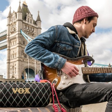 man playing electric guitar and using VOX AudioAir GT beside the Tower Bridge in London