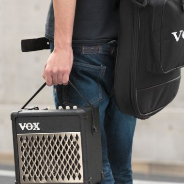 man carrying VOX amplifier and VOX gig bag