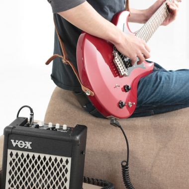 man playing red electric guitar beside VOX mini amplifier
