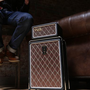partial view of man sitting on stool playing guitar beside VOX amplifier