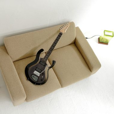 black VOX electric guitar on sofa